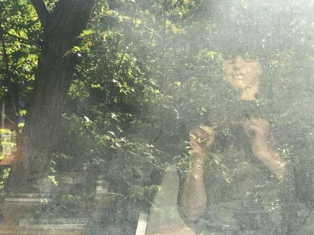 iPhone selfie in which my reflection is mingling with the image of the tree on the other side of the window.